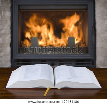 Open old book on the table and fireplace in the background - stock photo