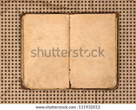 open old book over grungy textured polka dot background - stock photo