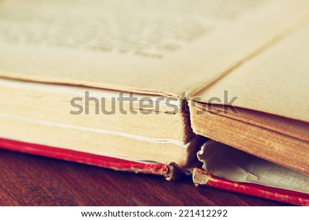 Open old book over wooden table. macro image with selective focuse. filterted image - stock photo