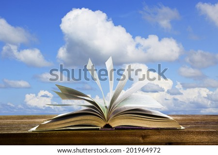 open old book page on wood table with flying book page against beautiful blue sky use for abstract education and idea creative school object - stock photo