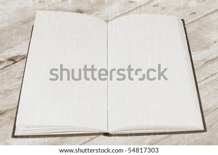 Open old book with blank pages on a wooden table (vintage style, with a grungy effect added) - stock photo