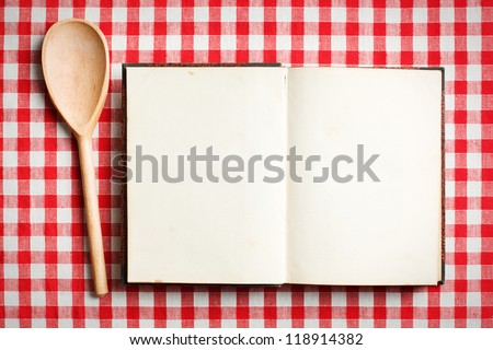 open old recipe book on checkered tablecloth - stock photo