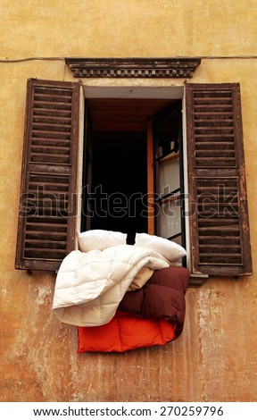 Open old window with wood shutters, grungy wall and bedclothes in small town, Italy - stock photo