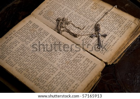Open pages of an ancient holy bible with a silver cross lying on it, image taken over dark old background