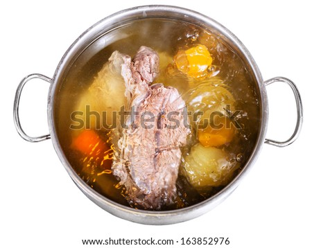 open pan with cooking beef broth with with seasoning vegetables isolated on white background - stock photo