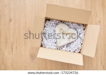 Open parcel box with a heart shaped Valentine's Day gift inside it. - stock photo