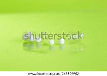 open pill with homeopathy globules in  green background  - stock photo