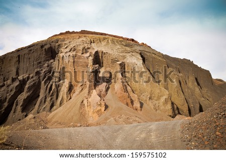 Open pit mine mountain. Lava and other building materials source. Fuerteventura - stock photo