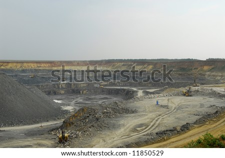 Open-pit mining for lignite (brown coal) that is burnt and transformed to electricity by the power station - stock photo