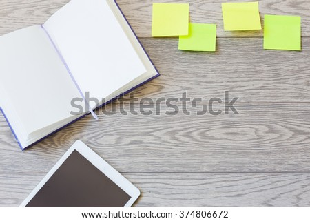 open plain notepad with tablet and sticky notes on wooden table top-view - stock photo