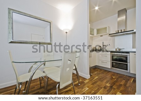 open plan kitchen with dining table and designer chairs - stock photo
