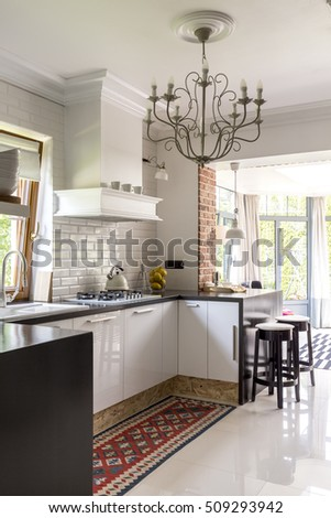 Open plan kitchen with white built-in furniture, patterned carpet, stylish chandelier and patio entry