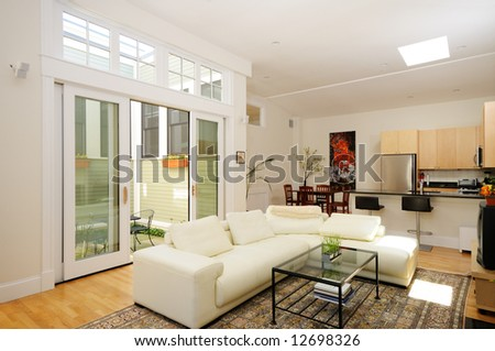 Open plan living room, dining room, kitchen and atrium in modern townhouse - stock photo
