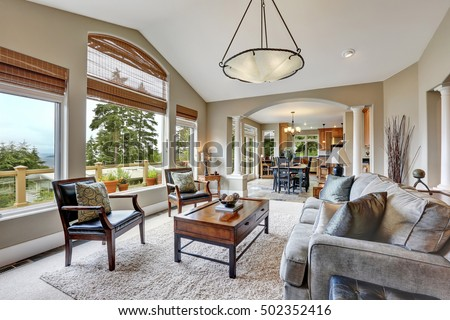 Open plan living room interior in luxurious house  with kitchen room in the background. Northwest, USA