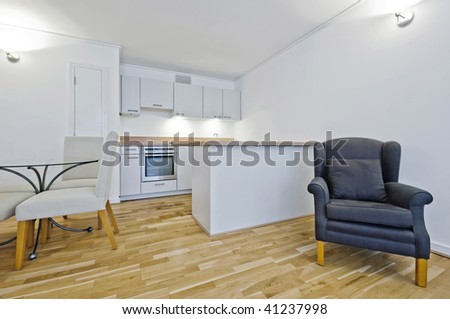 open plan lounge with dining table armchair and kitchen view - stock photo