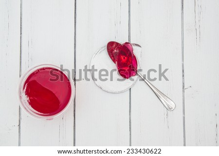 Open plastic container for dairy foods with red clear jelly pudding with foil lid and spoon. Isolated on a white. Top view - stock photo