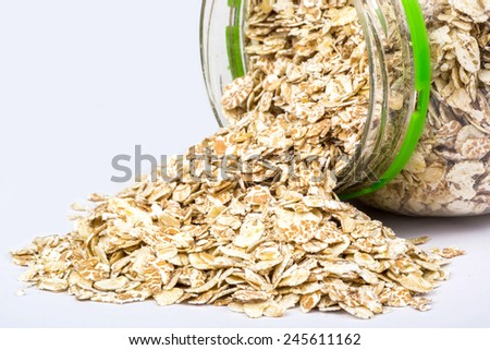 Open plastic jar with are scattered oatmeal - stock photo