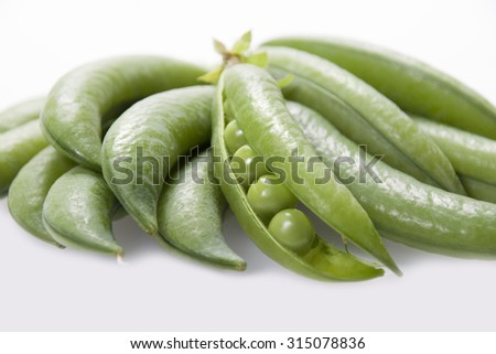 Open pod of peas on a white background close-up.