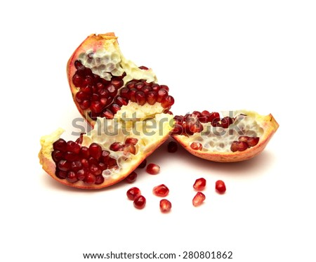 open pomegranate and scattered seeds on white background