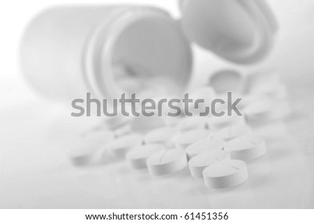 Open   prescription bottles  and white tablets  scattered on  table