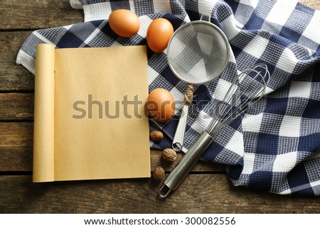Open recipe book, eggs and napkin on wooden background - stock photo