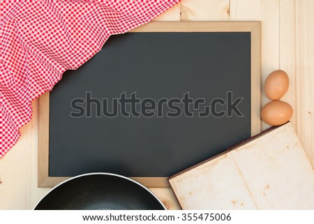 Open recipe book on a blackboard with a red checkered tablecloth - stock photo