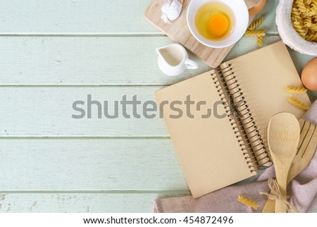 Open recipe book on green wooden table with copy space, Top view