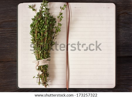 Open recipe book with bunch of thyme on a wooden background. - stock photo