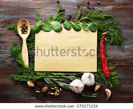Open recipe book with fresh herbs and spices on wooden background - stock photo