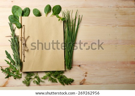 Open recipe book with fresh herbs on wooden background - stock photo