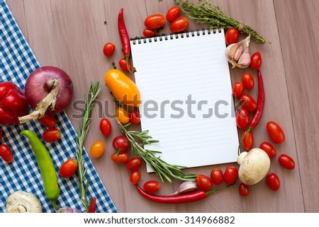 Open recipe book with fresh vegetables and herbs on wooden background.