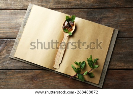 Open recipe book with mint leaves on wooden background - stock photo