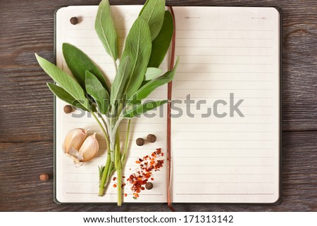 Open recipe book with sage and spices on a wooden background. - stock photo