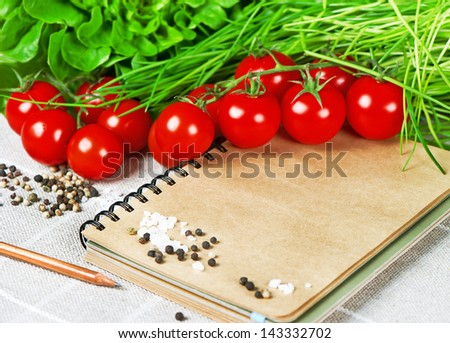 open recipe book with vegetables. tomatoes, chives and spices. healthy food