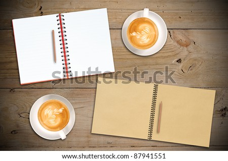 Open Red Notebook, Open Vintage Sketch Book, Penils with two cups of Latte on Old Wooden Table
