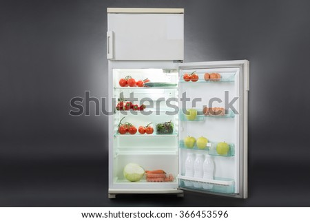 Open refrigerator full of fresh food isolated over gray background - stock photo