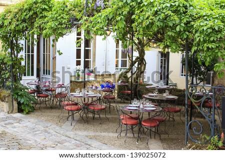 Open restaurant terrace under a grape vine in Saint-Emilion town, Gironde, France - stock photo