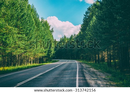 Open Road in future, no cars, auto on asphalt road through green forest, trees, pines, spruces. Clouds on blue sky in summer, sunshine, sunny day. Good weather. bokeh, blurred road vintage photo image - stock photo