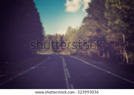 Open Road in future, no cars, auto on asphalt route through green forest, trees, pines, spruces. clouds on blue sky in summer, sunshine, sunny day. Good weather. bokeh, blurred road vintage photo - stock photo