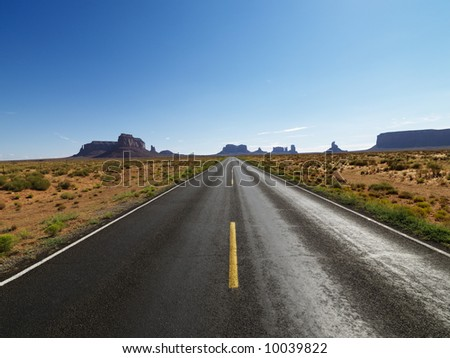 Open road in scenic desert landscape with distant mountains and mesas.