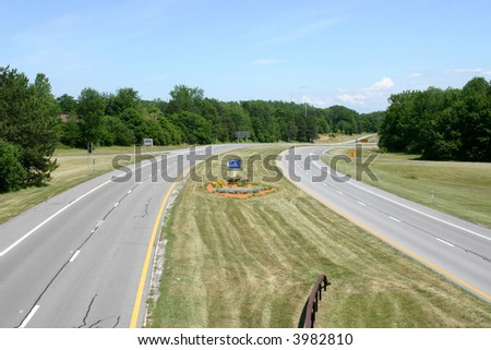 Open road with grass and trees but no cars - stock photo