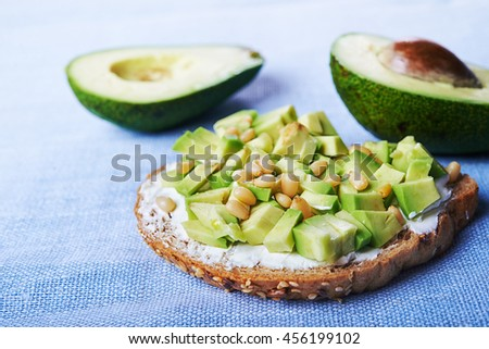 open sandwich with chopped avocado and cedar nuts - stock photo