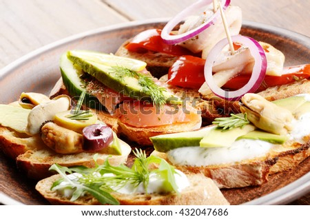 Open sandwiches with salmon, eggs, mussels, jamon and herring on ceramic plate