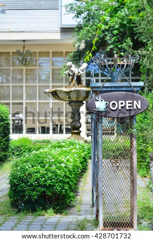 Open sign in front of garden and cafe