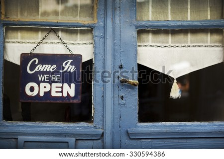 Open sign on the door of an old French bistro - stock photo