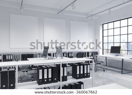 Open space office, big window to the right, New York view, tables with computers, office chairs, shelves with folders, lamps on the ceiling, three white boards on the wall. Concept of work