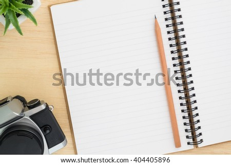 Open spiral notebook, empty line paper with brown pencil and vintage camera and small plant - notebook paper on wood background - working desk top view - stock photo