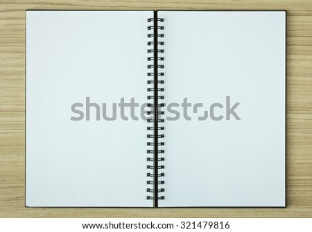 open spiral notebook on wood background - stock photo