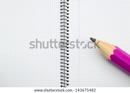 Open spiral notebook with giant pencil