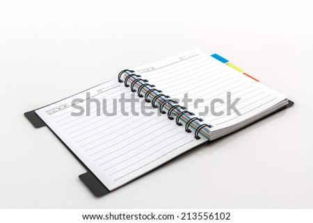 Open spiral notebook with lines on white background.